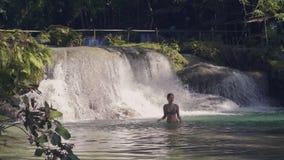 Joven bañándose en cascada en el bosque tropical y el arroyo de agua salpicándose en el fondo El agua fluida está en almacen de metraje de vídeo