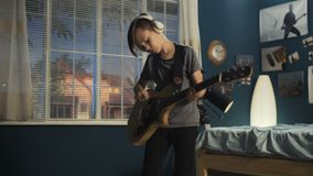 Joven con la guitarra en dormitorio almacen de metraje de vídeo