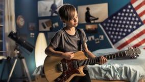 Joven con la guitarra en dormitorio Foto de archivo libre de regalías