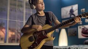 Joven con la guitarra en dormitorio Imagenes de archivo