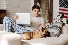 Joven encantado que pone la mano izquierda en su perro Fotos de archivo libres de regalías