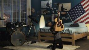 Joven expresivo que toca la guitarra en dormitorio metrajes