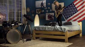 Joven expresivo que toca la guitarra en dormitorio fotos de archivo libres de regalías