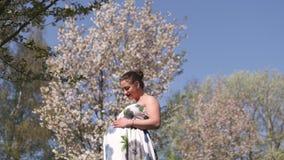 Joven feliz pronto a ser mam? de la madre - la mujer embarazada del viajero joven disfruta de su tiempo libre del ocio en un parq almacen de video