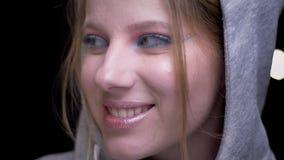 Joven femenino rubio en sudadera con capucha con maquillaje colorido que sonríe feliz en cámara en fondo borroso de las luces metrajes