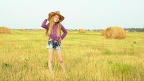 Joven modelo en sombrero de vaquero posando en el campo de cosecha en la aldea de otoño. Joven adolescente con vaquera buscando almacen de video