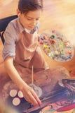 Joven sonriente que escucha la música mientras que pinta Imagenes de archivo