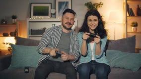 Jovens alegres que jogam os jogos de vídeo em casa que têm o divertimento tarde na noite vídeos de arquivo