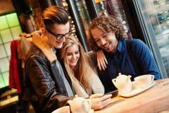 Jovens - amigos que têm o divertimento, olhando um telefone imagens de stock royalty free