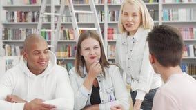 Jovens animados gostando de conversar na biblioteca da faculdade depois de estudar vídeos de arquivo