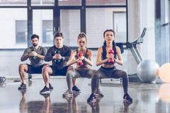 Jovens atléticos no sportswear com pesos que exercitam no gym fotografia de stock