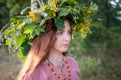 Jovens bonitos em um vestido de Viking Age e da grinalda das folhas e das flores do carvalho imagem de stock royalty free