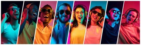 Jovens bonitos na luz de néon isolada no fundo colorido do estúdio fotos de stock