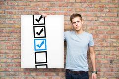 Jovens com as caixas de seleção no whiteboard Fotografia de Stock