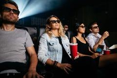 Jovens com bebidas que olham o filme 3d Fotografia de Stock Royalty Free