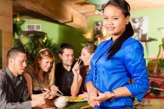 Jovens com a empregada de mesa no restaurante tailandês Imagens de Stock Royalty Free