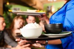 Jovens com a empregada de mesa que come no restaurante tailandês imagem de stock