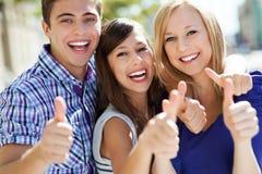 Jovens com polegares acima Fotografia de Stock