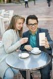 Jovens com telefone celular no café Fotografia de Stock Royalty Free