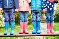 4 jovens crianças nos revestimentos, nas calças de brim e nos wellies Fotos de Stock Royalty Free