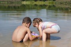 Jovens crianças que jogam na praia perto do lago. Foto de Stock Royalty Free