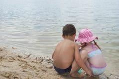 Jovens crianças que jogam na praia perto do lago. Imagem de Stock