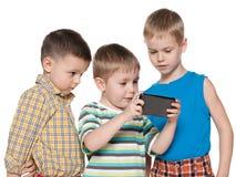Jovens crianças que plaing com um dispositivo novo Fotografia de Stock Royalty Free