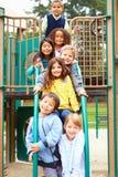 Jovens crianças que sentam-se no quadro de escalada no campo de jogos Foto de Stock