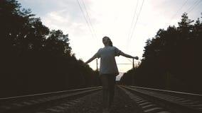 Jovens dançando krump entre a trilha ferroviária contra o sol, em câmera lenta video estoque