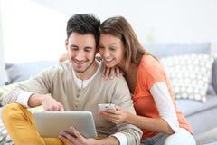 Jovens em casa conectados com a tabuleta Fotografia de Stock Royalty Free