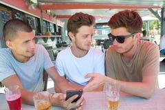 Jovens em fotos de observação da barra no telefone celular Imagens de Stock Royalty Free