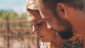 Jovens em pares do amor com o smartphone que senta-se no banco Dia ensolarado ventoso do verão video estoque