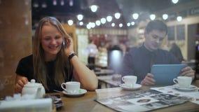 Jovens em um café com o PC do telefone e da tabuleta vídeos de arquivo