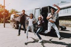 Jovens entusiasmados que saltam na frente do ônibus de excursão imagem de stock