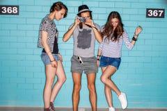 Jovens felizes com a câmera da foto que tem o divertimento na frente do azul Fotos de Stock Royalty Free