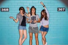 Jovens felizes com a câmera da foto que tem o divertimento na frente do azul Fotografia de Stock Royalty Free
