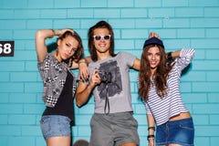 Jovens felizes com a câmera da foto que tem o divertimento na frente do azul Imagem de Stock