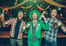 Jovens felizes e positivos para estar junto e cantar Excitaram Indivíduo no terno de St Patrick médio do desgaste foto de stock royalty free