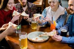 Jovens felizes multirraciais que comem a pizza na pizaria, amigos alegres que riem apreciando a refeição que tem o assento do div fotografia de stock royalty free