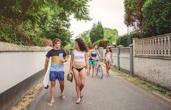 Jovens felizes que andam ao longo da estrada no dia de verão foto de stock royalty free