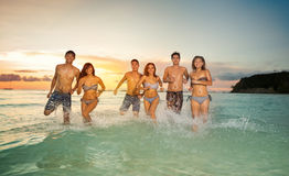Jovens felizes que jogam no mar Fotografia de Stock