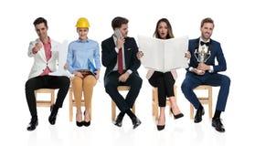 Jovens felizes que sentam e que esperam uma entrevista de trabalho imagens de stock