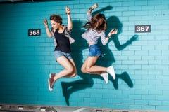 Jovens felizes que têm o divertimento e que saltam na frente do tijolo azul Imagens de Stock