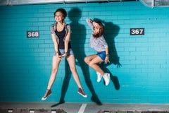 Jovens felizes que têm o divertimento e que saltam na frente do tijolo azul Fotografia de Stock