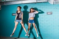 Jovens felizes que têm o divertimento e que saltam na frente do tijolo azul Foto de Stock