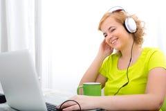 Jovens mais a mulher do tamanho que escuta o áudio ao trabalhar em um lapt foto de stock