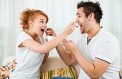 Jovens, menina da beleza e menino comendo o iogurte imagens de stock royalty free
