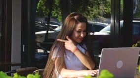 Jovens, mulher atrativa feliz que aprecia uma xícara de café em um café, datilografando em um portátil vídeos de arquivo
