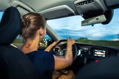 Jovens, mulher que conduz um carro no crepúsculo foto de stock
