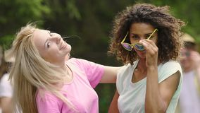 Jovens mulheres atrativas que retiram óculos de sol ao dançar alegremente no partido video estoque